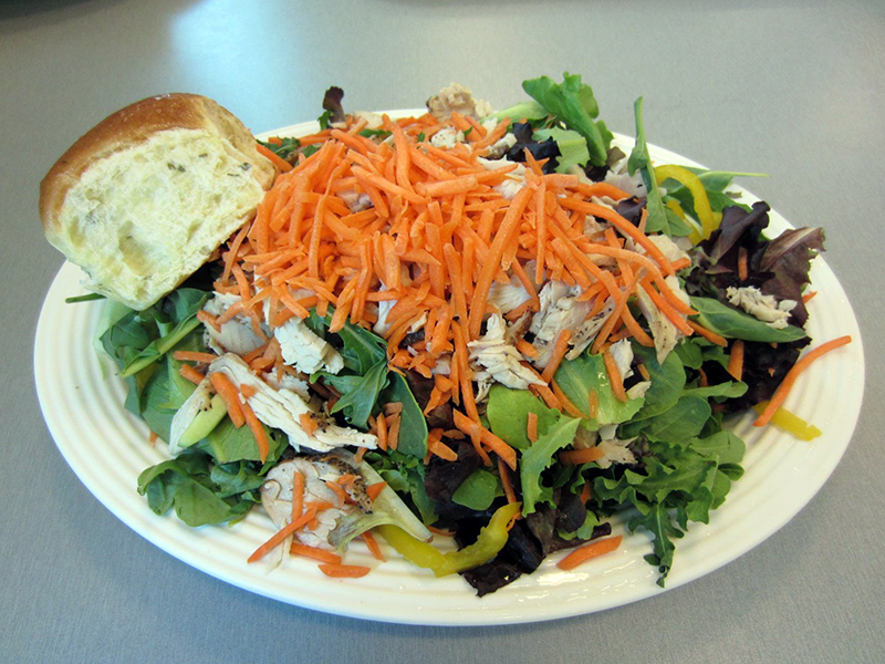 Citrus Turkey Salad contains mixed greens, arugula, julienned carrots, cucumbers, and yellow peppers with a citrus tarragon dressing and garlic chive roll on the side