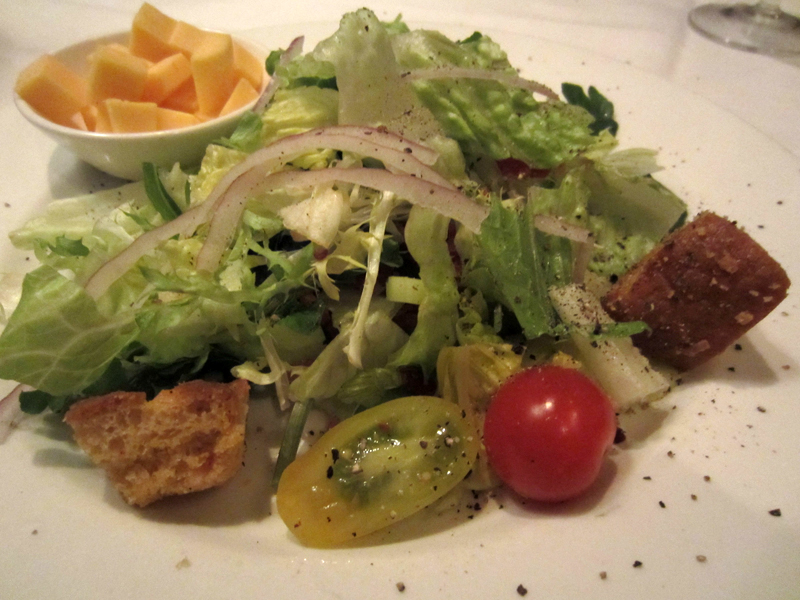 The Steakhouse Salad is served with bacon, cucumber, tomato, red onion, and Tillamook Cheddar cheese.