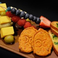 "Fruit and Cheese ""Sabers"" featuring Tillamook cheddar, Brie, goat cheese, pickled vegetables, crostini, cheddar crackers, blueberries, raspberries, honeydew melon, strawberry, olives and gherkins available at Rebel Hangar during Star Wars Weekends 2015"