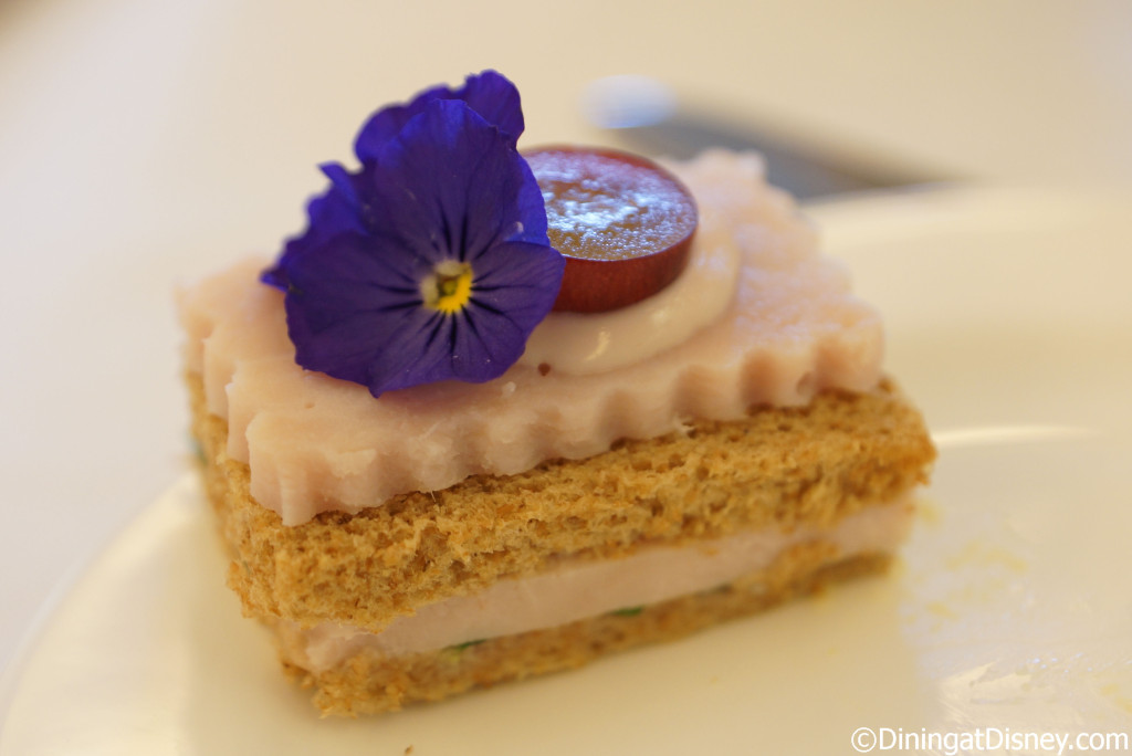 The turkey sandwich topped with a grape and edible flower at The Royal Tea at Peacock Alley, Waldorf Astoria Orlando